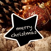 the text merry christmas written in a star-shaped chalkboard, on a rustic background with some logs, pine cones and some baubles
