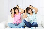 Beautiful girls twins sitting on sofa in room