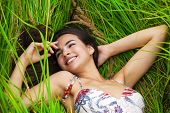 Happy woman resting and day lying down on green grass