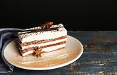 Tasty tiramisu cake on plate, on wooden table, on black background