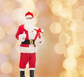 christmas, holidays and people concept - man in costume of santa claus with gift box showing thumbs up gesture over beige lights background