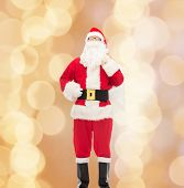 christmas, holidays and people concept - man in costume of santa claus with bag over beige lights background