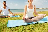 fitness, sport, people and lifestyle concept - close up of smiling couple making yoga exercises sitting on mats outdoors