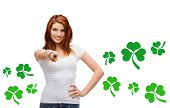 gestures, holidays, st. patricks day and people concept - happy teenager in blank white t-shirt pointing at you over white background with green shamrock or clover