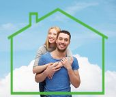 love, home, people and family concept - smiling couple hugging over green house and blue sky with cloud background