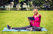 fitness, park, technology and sport concept - smiling african american woman with tablet pc and headphones showing thumbs up outdoors