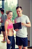 fitness, sport, exercising and diet concept - smiling young woman with personal trainer in gym