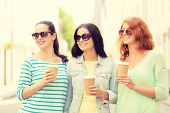 vacation, weekend, drinks and friendship concept - smiling teenage girls with coffee cups on street