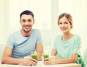 food, home, couple and happiness concept - smiling couple having breakfast at home