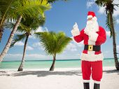 christmas, holidays, gesture and people concept - man in costume of santa claus pointing fingers over tropical beach background