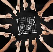 gesture, people, business and development concept - human hands showing thumbs up in circle over black board background with graph