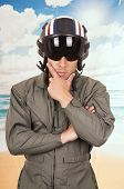 young handsome pilot wearing uniform and helmet over beach background