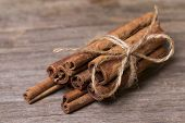 Cinnamon sticks close up on wooden background