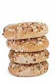 some brown bagels topped with different seeds, such as sesame and poppy seeds, on a white background