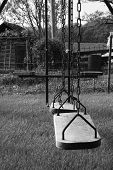 picture of swingset  - Black and white primitive swingset with rustic appeal.