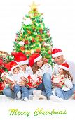 Happy family in Christmas eve at home sitting near decorated fir tree over white background, wearing red Santa hats opening presents, happiness and togetherness concept