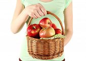 Woman holding red apples in wicker basket on white background