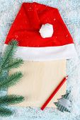 Santa red hat with fir-tree branch, sheet of paper, pencil  and snowflakes on color wooden background