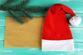 Santa red hat with fir-tree branch and sheet of paper on color wooden background