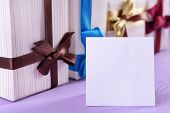 Cute presents with greeting card on light blue uneven background