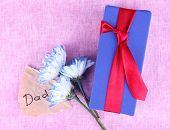 Happy Father's Day with gift box, flowers and piece of paper on texture background