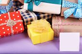 Pile of colorful gifts with greeting card on purple background