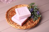 Bars of natural soap with fresh lavender on wicker mat, on wooden background