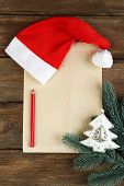 Santa red hat with branch of fir-tree, sheet of paper and pencil on wooden background