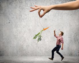 stock photo of dangling a carrot  - Young man in casual teased by carrot hanging on rope - JPG