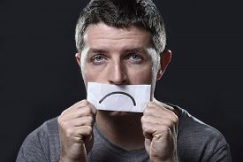 picture of sad  - young depressed man lost in sadness and sorrow holding paper with sad mouth draw on his mouth in stress grief depression and lost of hope concept isolated on black background - JPG
