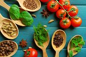 pic of spice  - Tomatoes with wooden spoons with fresh herbs and spices on wooden background - JPG