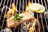 stock photo of flame-grilled  - Grilled salmon with lemon on the flaming grill - JPG