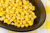 stock photo of sweet-corn  - Sweet canned corn in black oval glass dish closeup - JPG