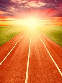pic of track field  - Running track in field with sky and clouds  - JPG