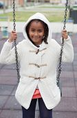 image of swing  - Outdoor portrait of a cute young black girl playing with a swing  - JPG