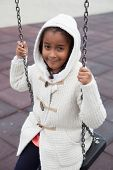 foto of swing  - Outdoor portrait of a cute young black girl playing with a swing  - JPG