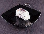 stock photo of ice-cake  - Ice cream cake slice over a black reflecting plate wooden table horizontal image - JPG