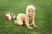 stock photo of crawling  - Cute happy smiling little baby girl in yellow clothing and funny hat with flower crawling in park on green grass - JPG