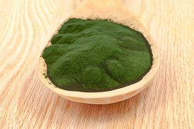 pic of algae  - Closeup of an organic spirulina algae powder and pills in a wooden spoon - JPG