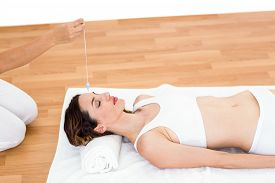 stock photo of hypnotic  - Woman being hypnotized while lying on the floor on white background - JPG