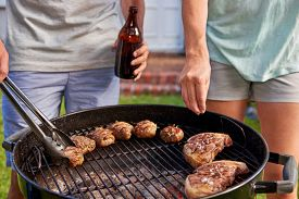 picture of braai  - Women seasoning meat on outdoor garden barbecue while man turns meat - JPG