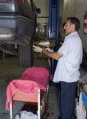 image of hookup  - a mechanic removes a tire from a car up on a lift - JPG