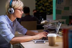 image of late 20s  - Female Office Worker With Coffee At Desk Working Late - JPG