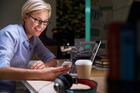 stock photo of late 20s  - Female Office Worker With Coffee At Desk Working Late - JPG