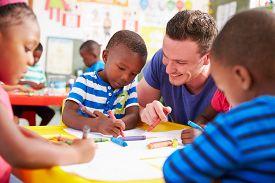 picture of teachers  - Volunteer teacher helping a class of preschool kids drawing - JPG