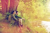 travel, hiking, backpacking, tourism and people concept - smiling couple with backpacks resting on r poster