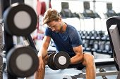 Young handsome man training at a fitness center. Fit guy lifting dumbbell at gym. Portrait of a youn poster