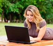Young pretty woman with laptop lying on the bench in a park