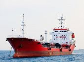 Red tanker is at anchor near the port.