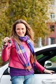 The happy woman showing the key of her new car.